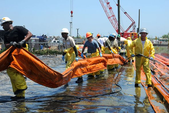 Workers carry an oil containment boom Venice, LA, May 4, 2010. Image from US Coast Guard and in public domain. Found here.