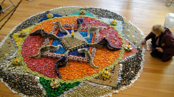 Bryant putting the finishing touches on a mandala made of bottle caps. Image credit: Bryant Holsenbeck's website.